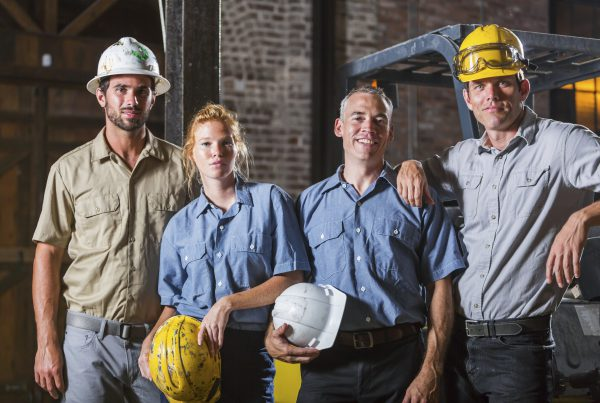 A group of four workers with hardhats, standing side by side, looking at the camera.