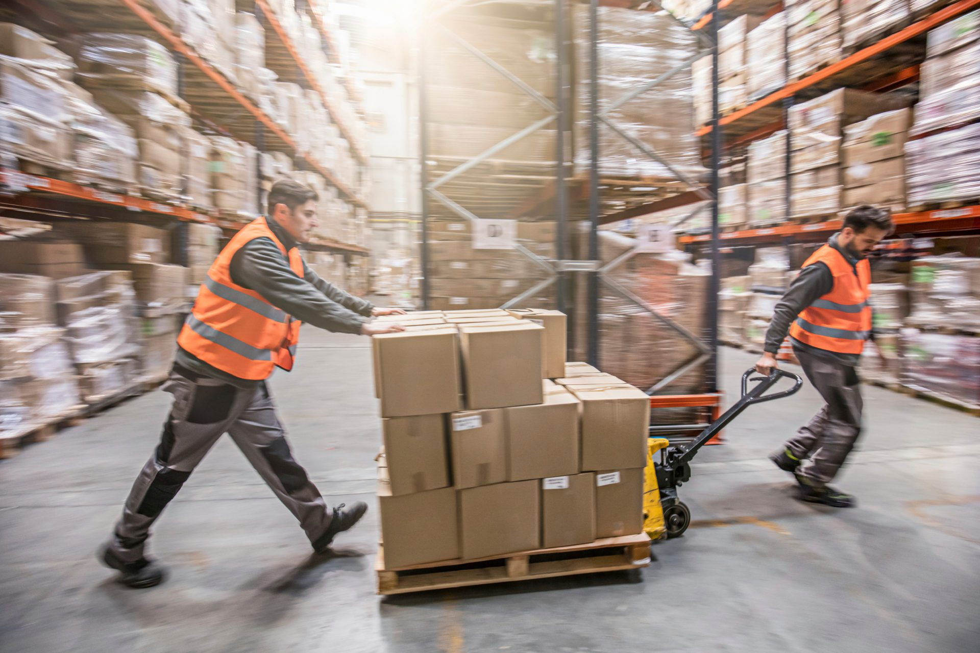 Motion blur of two men moving boxes in a warehouse